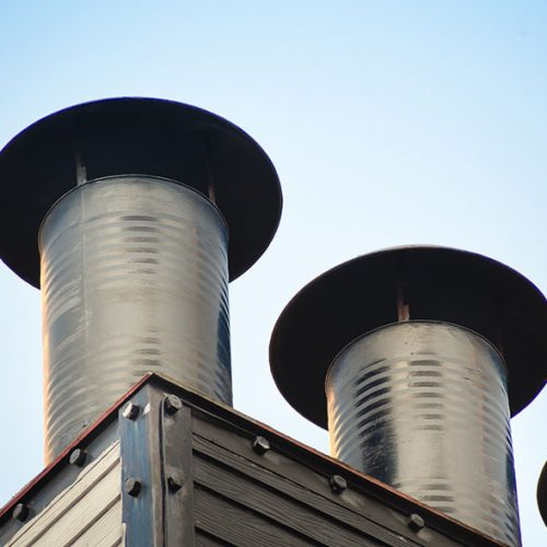 Aluminum ventilation chimneys Installed on the factory roof. Smokestack pipe for smoke out from kitchen house.